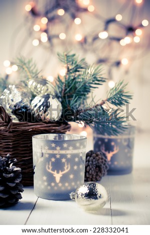 Vintage Christmas decor, old Christmas decorations in a basket, lanterns, garlands and spruce branches on a white table. - stock photo