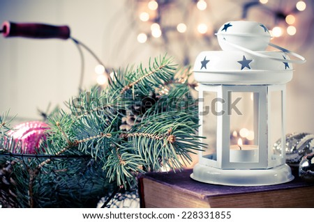 Vintage Christmas decor, old Christmas decorations, lanterns, garlands and spruce branches on a stack of books - stock photo
