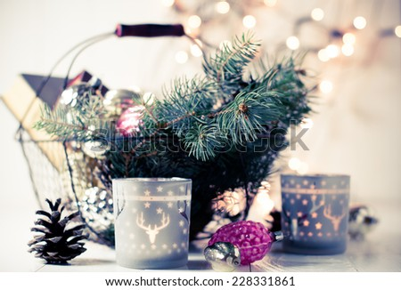 Vintage Christmas decor, old Christmas decorations, lanterns, garlands and spruce branches on a white table. Retro colors - stock photo