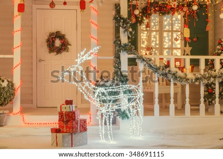 Vintage Christmas decorated house with illuminated deer in front of the door, gift boxes,  - stock photo