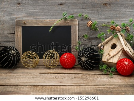 vintage christmas decoration with blackboard for your text over rustic wooden background. red and black china style balls and baubles - stock photo