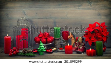 Vintage christmas decorations with red candles, flower poinsettia, stars and baubles. Retro style colored photo cross processing vignette - stock photo