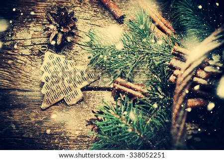 Vintage Christmas Metal Fir Tree Toy, Pine Cones, Cinnamon, Branches of Coniferous on Wooden Table. Rustic Style. Top view. Drawn Snow - stock photo