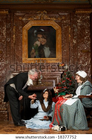 """Vintage Christmas scene of a Victorian family decorating a Christmas tree. Shot in castle """"Den Brandt"""" in Belgium (signed property release). The painting was replaced by a photo of one of the models. - stock photo"""