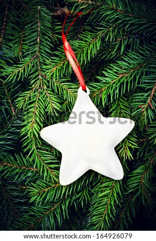 Vintage Christmas Star and red ribbon on fir  tree branches. Christmas fir tree background with  decoration. Christmas Card. - stock photo