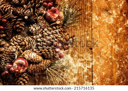 Vintage Christmas wreath with pine cones, sugared apples and red berries hanging on the grungy wooden door. Greeting card. Retro aged photo with scratches. - stock photo