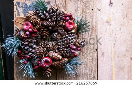 Vintage Christmas wreath with pine cones, sugared apples and red berries hanging on the grungy wooden door. Greeting card.