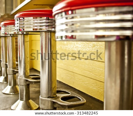 Vintage chrome deco diner chairs with red vinyl seats.  Yellow background - stock photo
