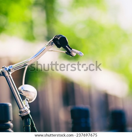 Vintage city bike colorful retro light and handlebar on street, cycling to work, commute on classic bicycle in urban environment, colorful green background