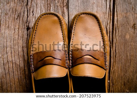 Vintage Classic Brown Leather Loafer Shoes Unique Style, Handmade Craftsmanship on Wood Stand Background, Rustic Still Life Style. - stock photo