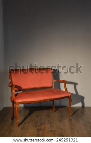 Vintage. Classic red elegant couch standing against grey wall - stock photo