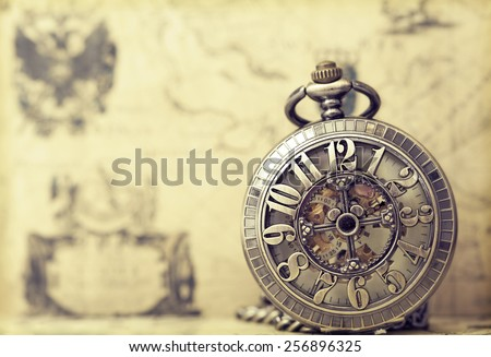 Vintage clock on antique map. Retro still life - stock photo