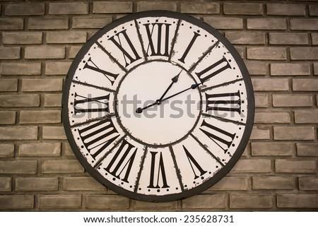 vintage clock on brick wall - stock photo
