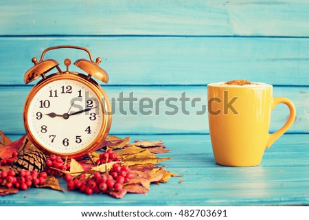 Vintage clock over autumn leafs and coffee cup