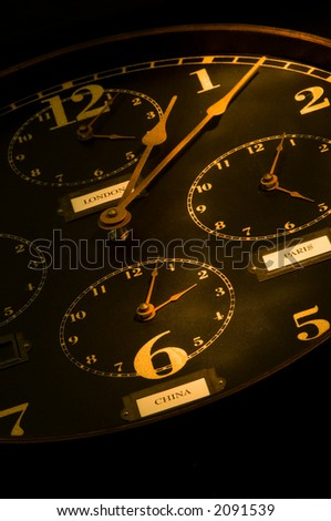 vintage clock with multiple faces depicting time in different parts of the world light painted with flashlight. - stock photo