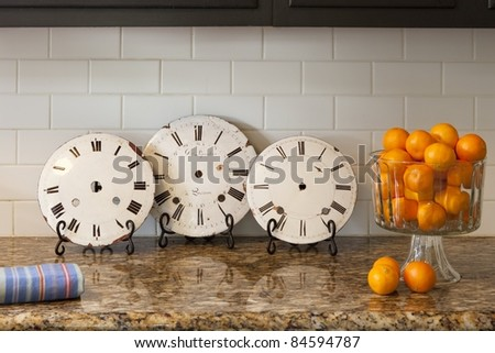 Vintage clocks on a counter with oranges and a towel - stock photo