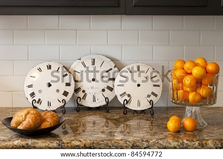 Vintage clocks on a counter with oranges and croissants - stock photo