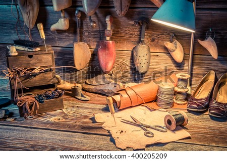 Vintage cobbler workshop with tools, shoes and leather - stock photo