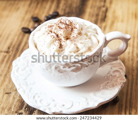Vintage Coffee Cup with Cappuccino and Whipped Cream on Wooden Background