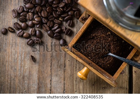 Vintage coffee grinder and beans on wooden background