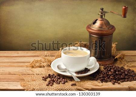 Vintage coffee grinder and coffee cup over wooden background over grunge background - stock photo