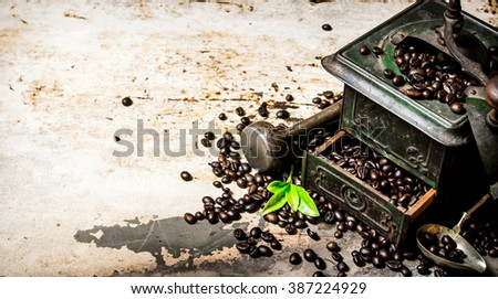 Vintage coffee grinder with pestle and roasted coffee beans. On rustic background. - stock photo