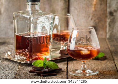 Vintage cognac still life with chocolate on wooden background - stock photo