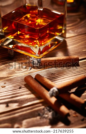 Vintage cognac with cigar over wooden background
