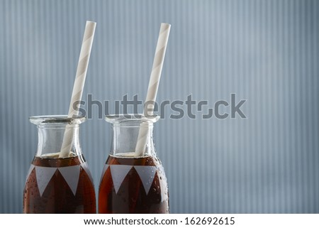 Vintage cola drink bottles with straws and copy space on a grungy blue striped background - stock photo