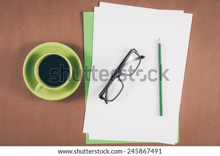 Vintage color. Mobile with blank paper or notebook and cup of coffee. Simple workspace or coffee break with relaxing composing. Blank paper and colorful pencils on the wooden table. View from above - stock photo