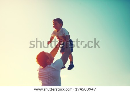 Vintage color photo happy joyful father having fun throws up in the air child, family, travel, vacation, father's day - concept. Sunlight on the sunset - stock photo