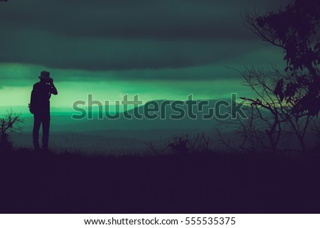 Vintage color silhouette shadow of traveler photography a mountain landscape under rainy clouds