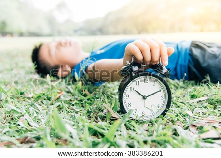 Vintage color tone, Selective focus on the classical black alarm clock model, in front of the sleeping young boy that try to stop the ring by his hand on green lawn, in the park in day time. - stock photo