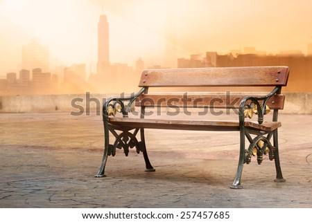 vintage color tone style of wooden bench antique with sunrise on flat top of a roof, soft focus  - stock photo