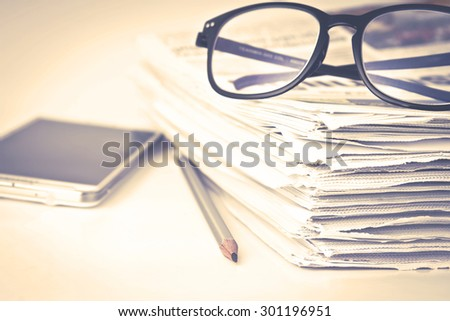 vintage color tone the reading eyeglasses with stacking of newspaper background ,  business information concept - stock photo