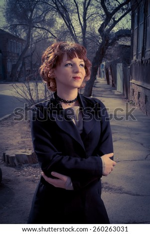 Vintage colored photo of redhead women posing outdoors. - stock photo