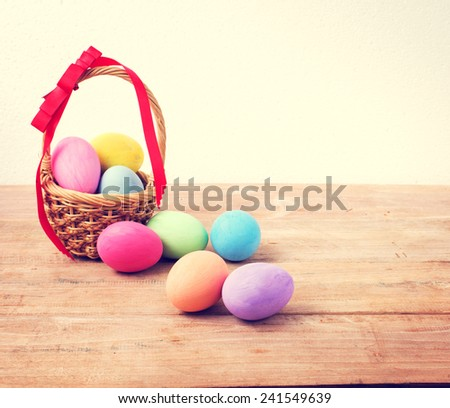 Vintage colorful easter eggs in basket on wood table background - stock photo