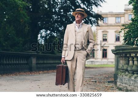 Vintage commercial traveler leaving his estate walking towards camera. - stock photo