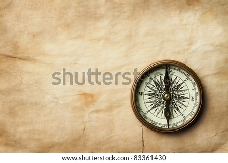 Vintage compass at old crumpled paper with copy space - stock photo