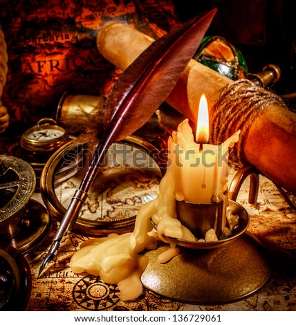 Vintage compass, magnifying glass, pocket watch, quill pen, spyglass lie on an old ancient map with a lit candle - stock photo