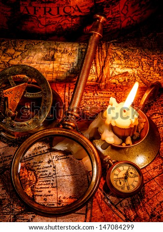 Vintage compass, magnifying glass, pocket watch, spyglass lie on an old ancient map with a lit candle. Vintage still life. - stock photo