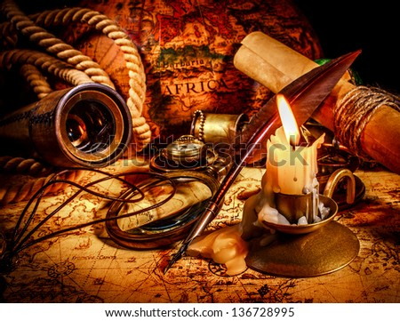 Vintage compass, magnifying glass, quill pen, spyglass lie on an old ancient map with a lit candle. Vintage still life. - stock photo