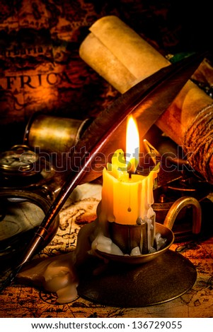 Vintage compass, magnifying glass, quill pen, spyglass lie on an old ancient map with a lit candle - stock photo