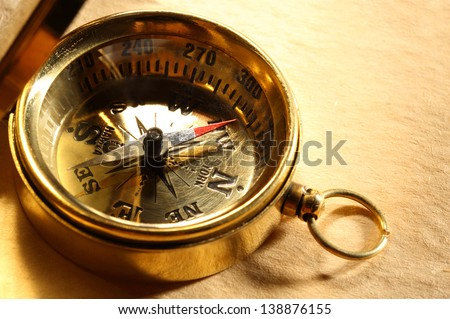 Vintage compass on blank yellowed paper - stock photo