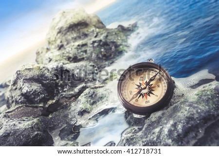 vintage compass on rocks at the shore - stock photo