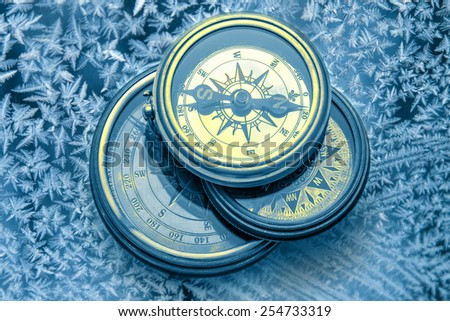 Vintage compass on snowflakes in blue toning - stock photo