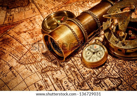 Vintage compass, , spyglass and a pocket watch lying on an old map. - stock photo