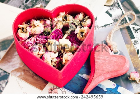 vintage concept   heart with dry flowers  on pile of old photos and key - stock photo