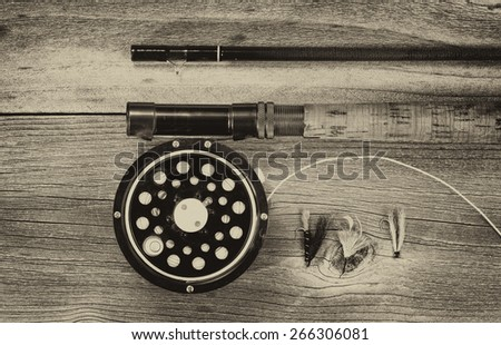 Vintage concept of an antique fly fishing reel and rod on rustic wood. Layout in horizontal format. - stock photo