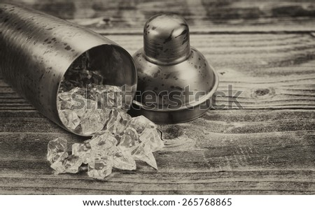 Vintage concept of an old metal drink mixer lying on side with crushed ice spilling out onto rustic wood - stock photo